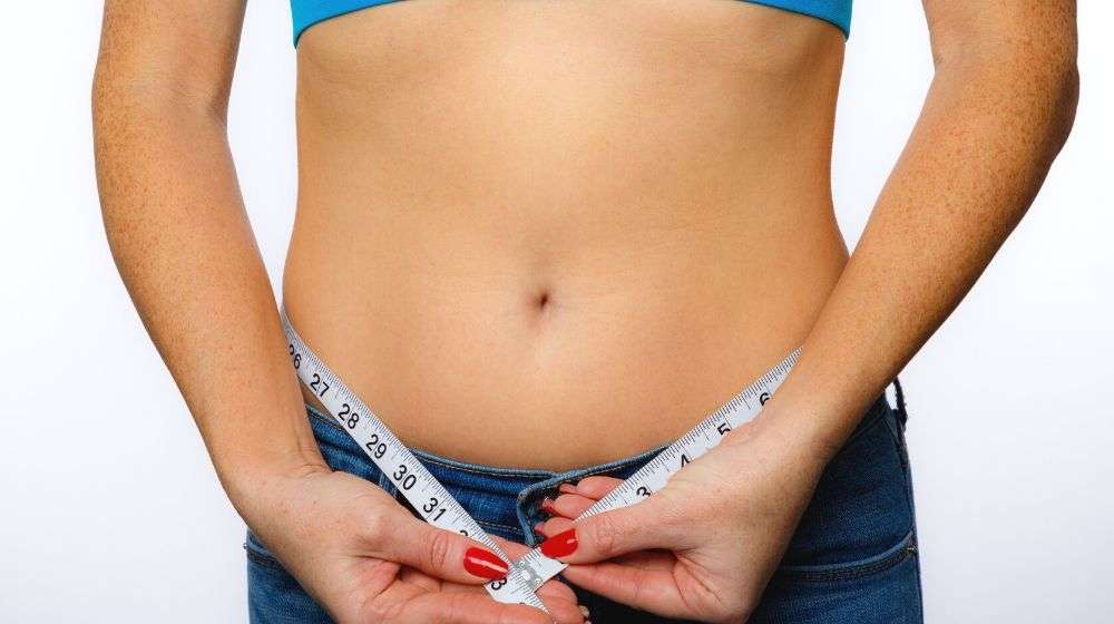 Woman In Jeans And Sports Bra With Measuring Tape | Feature | Em-Sculpt Non Invasive Body Contouring