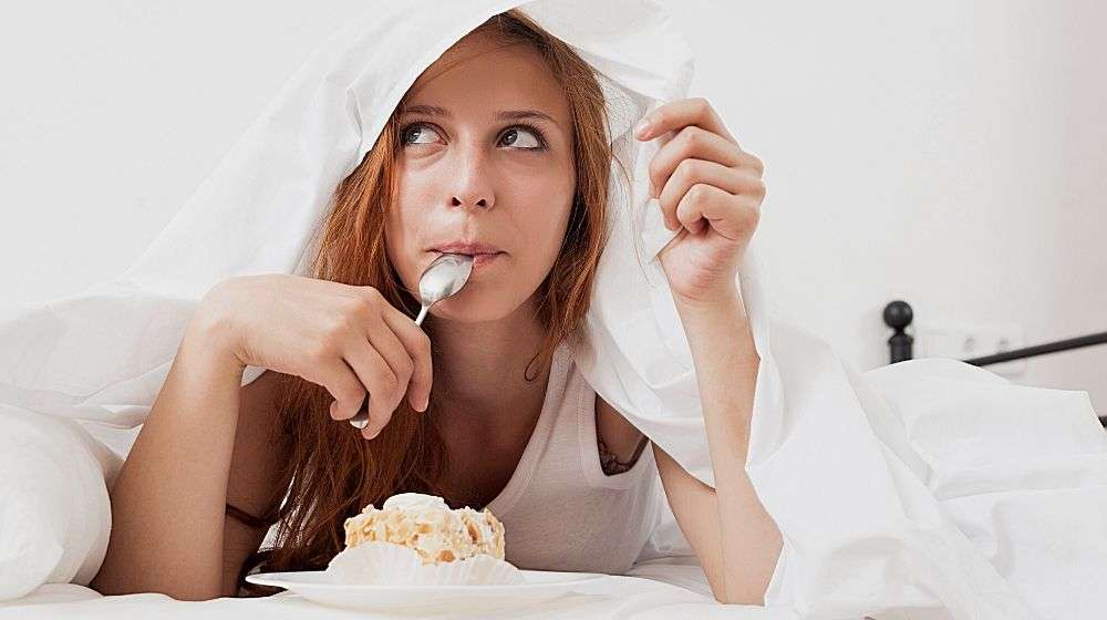 A girl eating a cake under the blanket | Feature | The Connection Between Diet and Sleep [INTERVIEW]