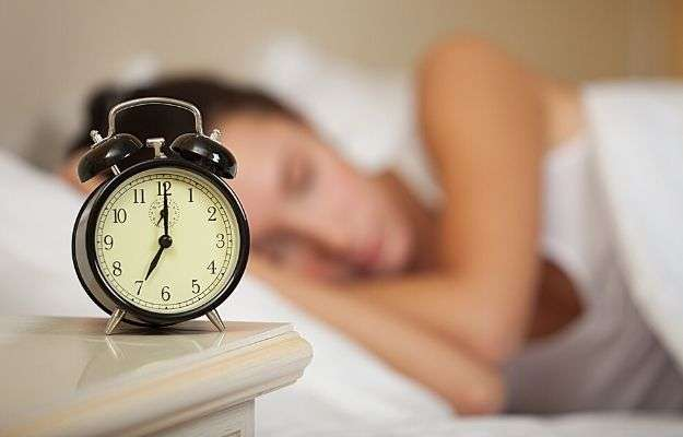 A woman sleeping next to the clock | Do Different People Need Different Amounts of Sleep? | The Connection Between Diet and Sleep [INTERVIEW]